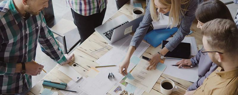 Menschen am Tisch mit Fotos und Statistiken
